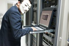 Masked Hacker in Computer Server room Concept . Stock Photos