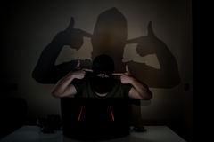 Dangerous internet hacker threatening a victim. A masked hacker hiding his face with a black scarf and trying to crack a online site in the dark. Big shadow Royalty Free Stock Photography