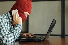 Masked hacker with mobile smart phone and laptop stealing important information data. Network security and privacy crime concept. Masked hacker with mobile Royalty Free Stock Photography