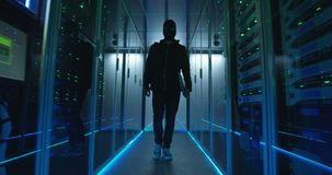 Masked hacker walking through rows of servers. Wide view, slow motion shot of a masked hacker walking through corporate data center with rows of working rack stock video footage