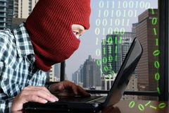 Masked hacker wearing a balaclava hacking data from laptop against digital city background Stock Image