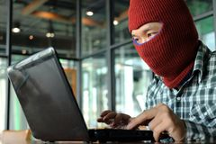 Masked hacker wearing a balaclava looking a laptop and stealing important information data. Network security and privacy crime con Royalty Free Stock Photography