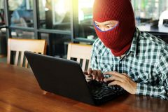 Masked hacker wearing a balaclava stealing data from laptop. Internet crime concept. Masked hacker wearing a balaclava stealing data from laptop. Internet crime Stock Image