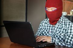 Masked hacker wearing a balaclava stealing data from laptop. Internet crime concept. Masked hacker wearing a balaclava stealing data from laptop. Internet crime Royalty Free Stock Images