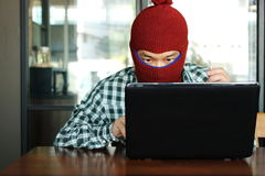 Masked hacker wearing a balaclava stealing data from laptop. Internet security concept. Masked hacker wearing a balaclava stealing data from laptop. Internet Stock Photos