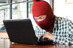 Masked hacker wearing a balaclava stealing importance data from laptop. Internet crime concept. Masked hacker wearing a balaclava stealing importance data from stock images