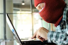 Masked hacker wearing a balaclava stealing importance data from laptop. Internet crime concept. Masked hacker wearing a balaclava stealing importance data from royalty free stock image