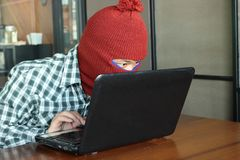 Masked hacker wearing a balaclava stealing important information data against laptop. Computer criminal concept. Royalty Free Stock Images