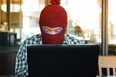 Masked hacker wearing a balaclava stealing information data with laptop. Computer criminal concept. Stock Image