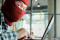 Masked hacker wearing a balaclava using laptop stealing important information data. Internet security and privacy crime concept. S. Elective focus and shallow stock photo