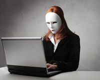 Masked identity. Young woman wearing a mask and using a laptop royalty free stock photo