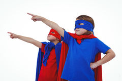 Masked kids pretending to be superheroes. Masked kids pointing somewhere pretending to be superheroes on white screen Stock Images