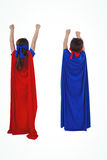 Masked kids pretending to be superheroes. Rear view of masked kids pretending to be superheroes on white screen Royalty Free Stock Image