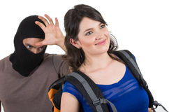 Masked male thief robbing beautiful young girl. Masked male thief robbing beautiful young happy girl carrying backpack from behind Royalty Free Stock Image