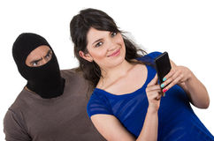 Masked male thief robbing beautiful young girl. Masked male thief robbing beautiful young happy girl talking on cell phone from behind Royalty Free Stock Photos