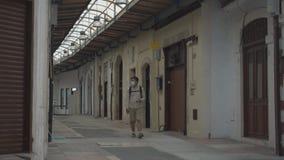 Masked male tourist walks at closed market during coronavirus pandemic, lockdown on Cyprus. Man in mask walks through