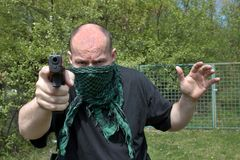 Masked man aims with gun Stock Photography