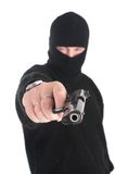 Masked man aims from gun in you. Focus on gun Stock Photos