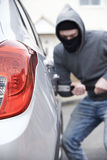 Masked Man Breaking Into Car With Crowbar Royalty Free Stock Photography
