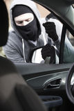 Masked Man Breaking Into Car With Crowbar Stock Photography