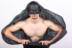 Masked man with cape. Portrait of half naked man with black mask and cape Royalty Free Stock Photos