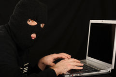 Masked man and computer. Masked man using a laptop computer as in internet fraud Royalty Free Stock Image