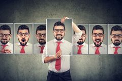 Masked man expressing different emotions. Masked young business man expressing different emotions and feelings on gray background stock image