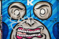 Masked man graffiti looking angry. Urban art in Shoreditch, London. Masked angry man showing teeth Stock Photography