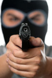 Masked Man With a Gun. An angry looking man wearing a ski mask pointing a black handgun at the viewer. Works great for crime or home security concepts Stock Images