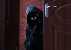 Masked man with gun spying behind open door. Criminal offence. Masked man with gun spying behind open door indoors. Criminal offence stock images