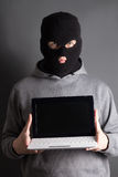 Masked man with computer over grey. Masked man with laptop over grey Royalty Free Stock Photography