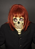 Masked man - skeleton in red wig Royalty Free Stock Images
