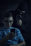 Masked man spying data from smartphone of teen Stock Photos