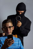 Masked man spying data from smartphone of teen Stock Images
