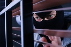 Masked man spying through window blinds. Criminal offence. Masked man spying through window blinds indoors. Criminal offence royalty free stock photos