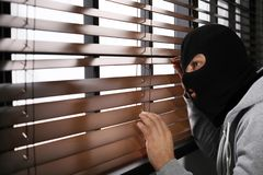 Masked man spying through window blinds. Criminal offence. Masked man spying through window blinds indoors. Criminal offence stock image