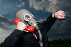 Masked man with telephone. The time has come.  A man wearing a gas mask is looking at his watch while making an important call on the red phone Royalty Free Stock Photo