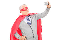 Masked mature man taking a selfie. Masked mature man with cape taking a selfie isolated on white background Stock Photography