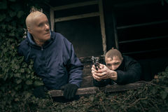 Masked men with a gun. Two masked armed men hiding on overgrown porch of old cabin royalty free stock photography