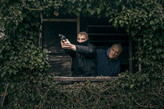 Masked men with a gun. Two masked armed men hiding on overgrown porch of old cabin royalty free stock photos