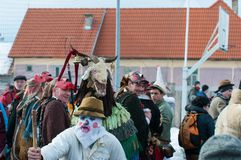 Masked men with his goat on the winter ending Transylvanian traditional carnival. Crowd Stock Photos