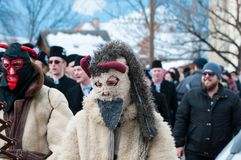 Masked men portrait on the winter ending Transylvanian traditional carnival. Crowd Stock Photography