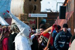 Masked men sharpens the wooden scythe. On the winter ending Transylvanian traditional carnival crowd Royalty Free Stock Photography