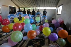 Masked Palestinians of the Popular Resistance Committees prepare incendiary balloons to be flown towards Israel