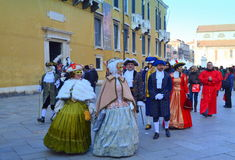 Masked people  procession Venice  street. Spectacular procession of disguised people talking friendly at Venice street,Italy Royalty Free Stock Photos