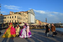 Masked people at Venice waterfront Royalty Free Stock Image