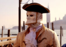 Masked person in costume on pier in St. Mark's Square during the Stock Photo