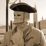 Masked person in costume on pier in St. Mark's Square during the Royalty Free Stock Photography
