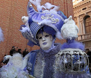 Masked person in magnificent lilac costume on San Marco Square i Stock Photography