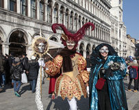 Masked persons in beautiful medieval costume on San Marco Square Stock Photo